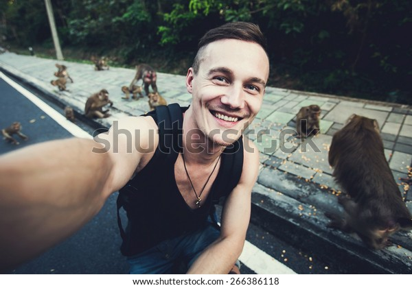 Handsome traveling man takes selfie photo with wild monkeys in tropical jungle forest in Phuket, Thailand, Asia