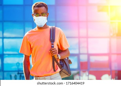 handsome trendy African Americans nerd male with glasses in stylish clothes colorful T-shirt with a backpack on the shoulders stand against the background of the blue windows airport