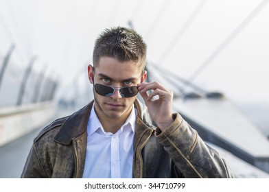 Handsome trendy young man standing on a sidewalk, wearing sunglasses and a fashionable leather jacket, in a relaxed confident pose looking at camera over the glasses
