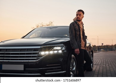 Handsome unshaved man in fashionable clothes standing near his black car and smoking.