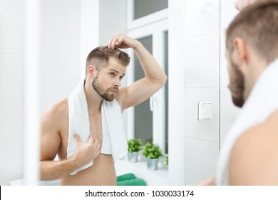 Handsome unshaven man looking into the mirror in bathroom
