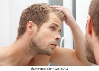 Handsome unshaven man looking into the mirror in bathroom