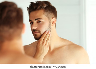 Handsome unshaven man looking in mirror