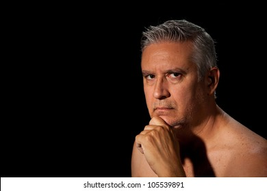 Handsome unshaven middle age man with salt and pepper hair and bare chested on a black background.