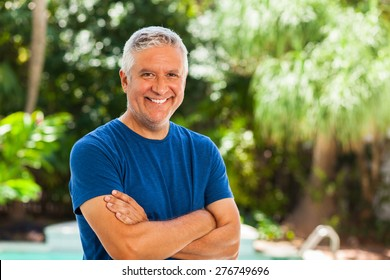 Handsome unshaven middle age man outdoor portrait with a green background.