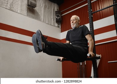 Handsome usnhaven retired man in stylish sportswear doing crossfit training in gym, raising legs while exercising on pull up bar, strengthening abdominals. Fitness, sports and retirement concept
