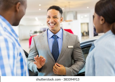 handsome vehicle dealer talking to customers in showroom