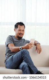 Handsome Vietnamese man with smartphone resting on sofa