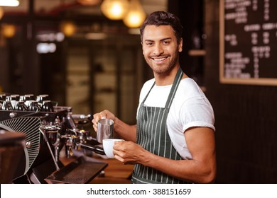 Handsome waiter adding milk to coffee at the cafe