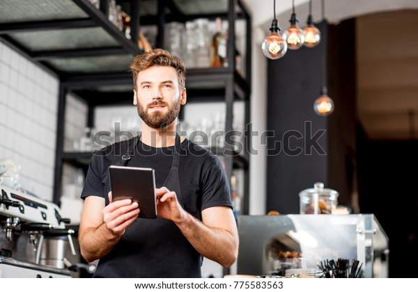 Handsome waiter in black t-shirt working with tablet standing at the bar of the modern cafe interior