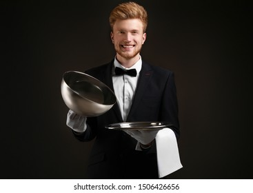 Handsome waiter with empty tray and cloche on dark background