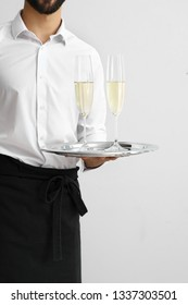 Handsome waiter with glasses of champagne on light background