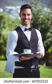 Handsome waiter holding a tray with cup of coffee outside