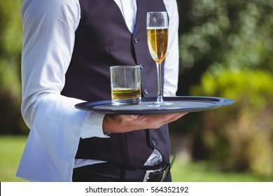 Handsome waiter holding a tray with drinks outside