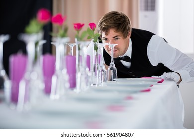 Handsome Waiter Looking At Wedding Table Arrangement At Restaurant