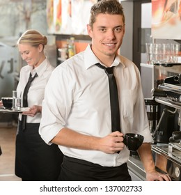 Handsome waiter making coffee with espresso machine in coffee house