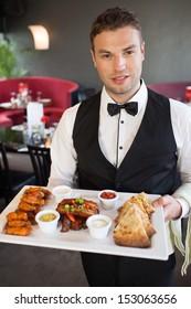 Handsome waiter serving appetizing finger food platter in classy restaurant