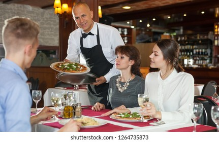Handsome waiter serving pizza to friendly company at stylish restaurant