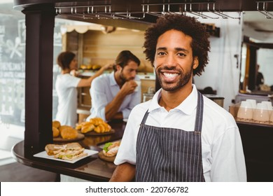 Handsome waiter smiling at camera at the coffee shop