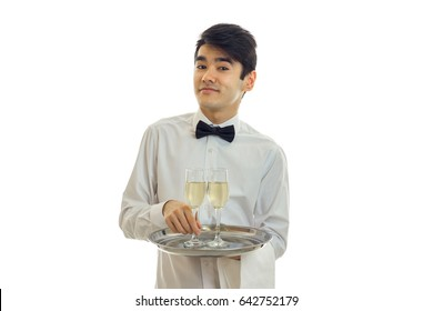 handsome waiter smiling in a white shirt looks straight and holding a tray with two glasses of wine