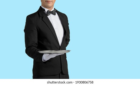 Handsome waiter in tuxedo and gloves holding empty tray and napkin whit dicut part.