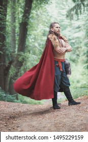 Handsome Warrior Viking man in fluttering cloak standing outdoor
