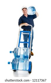 Handsome water delivery man with a five gallon jug on his shoulder and two more in the dolly.  Full body isolated on white.