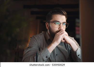 Handsome web designer dressed in shirt and wearing eyeglasses working late at night and looking at computer.
