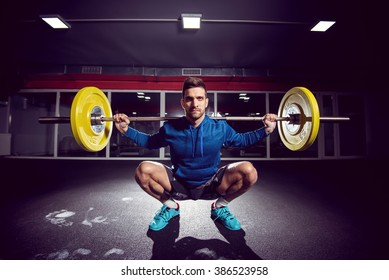Handsome weightlifter at gym doing squats.