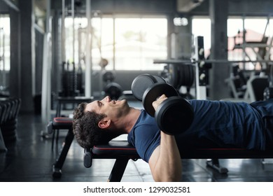 Handsome weightlifter lifting bench press working out with dumbbell in the gym.