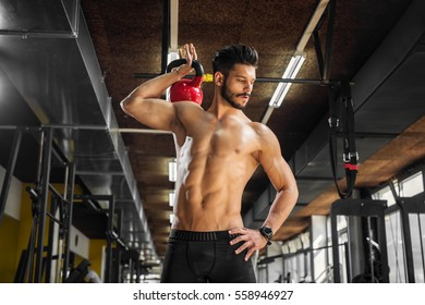 Handsome weightlifter working out at the gym using a kettlebell.
