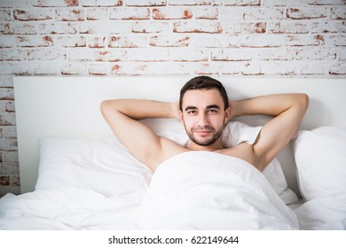 Handsome well built man resting in his bed
