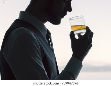 Handsome well dressed professional man silhouetted profile holding a neat whiskey scotch drunk backlit in white.