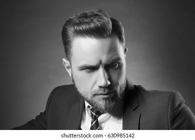 Handsome well-dressed in blue suit and tie man with perfect hair style and beard. Studio portrait. Black and white