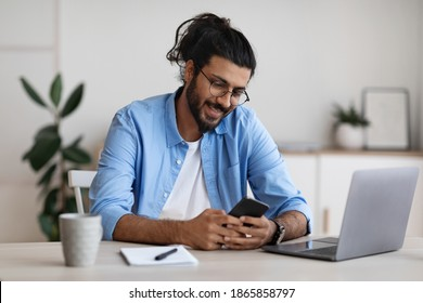 Handsome western freelancer guy sitting at desk at home office and using smartphone, messaging with friends, checking social media or browsing new app, enjoying mobile communication, free space - Shutterstock ID 1865858797