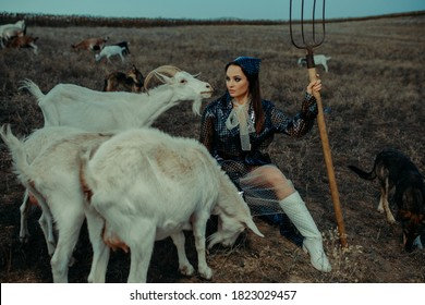 Handsome woman farmer sits in raincoat with pitchfork in her hand among a herd of goats on pasture.