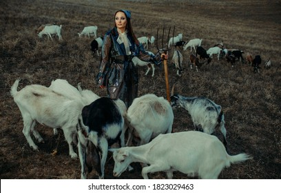Handsome woman farmer stands in raincoat with pitchfork in her hand among a herd of goats on pasture.