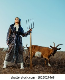 Handsome woman farmer stands in raincoat with pitchfork in her hand near goats on pasture.