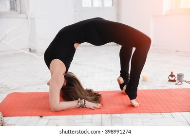 Handsome woman having yoga trainig on red gymnastic carpet in white lit room. Concept of physical and mental health, happy living and well being.