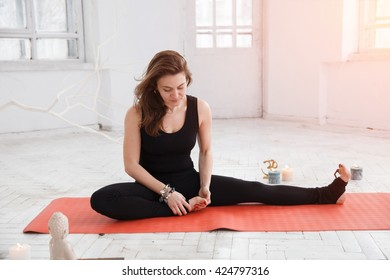 Handsome woman having yoga trainig on red gymnastic carpet in white lit room. Concept of physical and mental health, happy living and wellbeing.