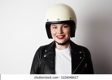 Handsome woman wearing black leather jacket and white moto helmet over background. Fashion, glamour and moto wear concept