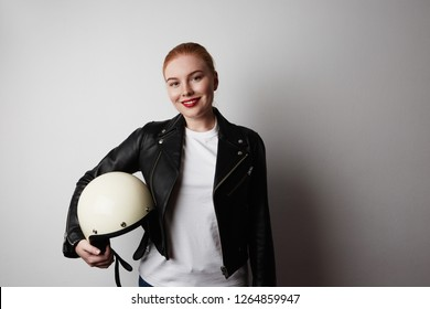 Handsome woman wearing black leather jacket and white moto helmet over background. Fashion, glamour and moto wear concept. Background.