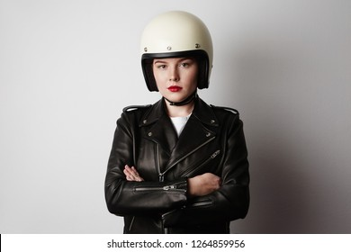 Handsome woman wearing black leather jacket and white moto helmet over background. Background