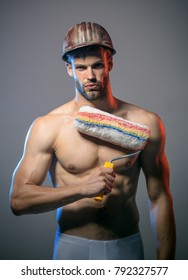 Handsome worker with paint roller. Painter man. Muscular painter man holding paint roller. Professional interior construction worker. Handsome bearded worker with paint roller.