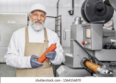 Handsome worker standing near modern new equipment for sausage production, holding sausage, looking at camera, posing. Food industry. Elderly man wearing in white uniform and apron.
