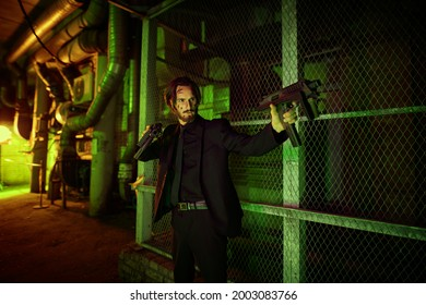Handsome wounded man special agent. Courageous action hero with automatic guns in an industrial zone at night.