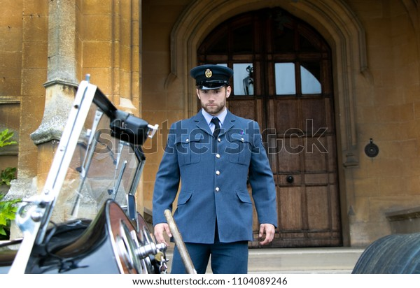 Handsome WWII, Air force corporal in blue uniform leaves English headquarter building and boards his blue vintage sports car