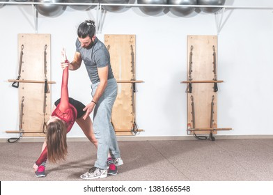 Handsome yoga male personal trainer with a beard helping young fitness positive girl to stretch her muscles after hard training workout, real people no posing, selective focus