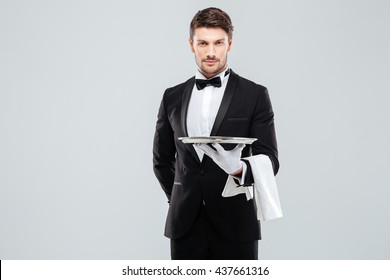 Handsome yong waiter in tuxedo and gloves holding empty tray and napkin