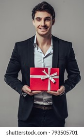 Handsome yound man in suit is posing on grey background with red gift box in hands, looking at camera and smiling.